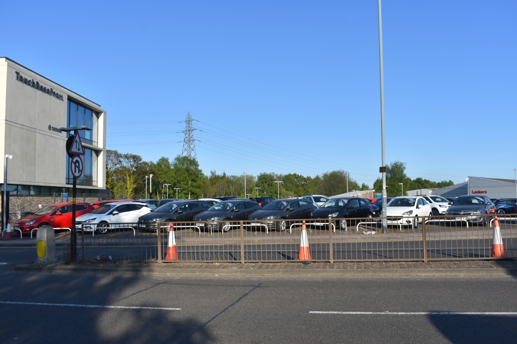 Car dealership adjacent to suburban A Road. A road in foreground including railings. Car forecourt with new and used cars for sale in foreground alongside corner of three storey office block. Trees and an electricity pylon in the background