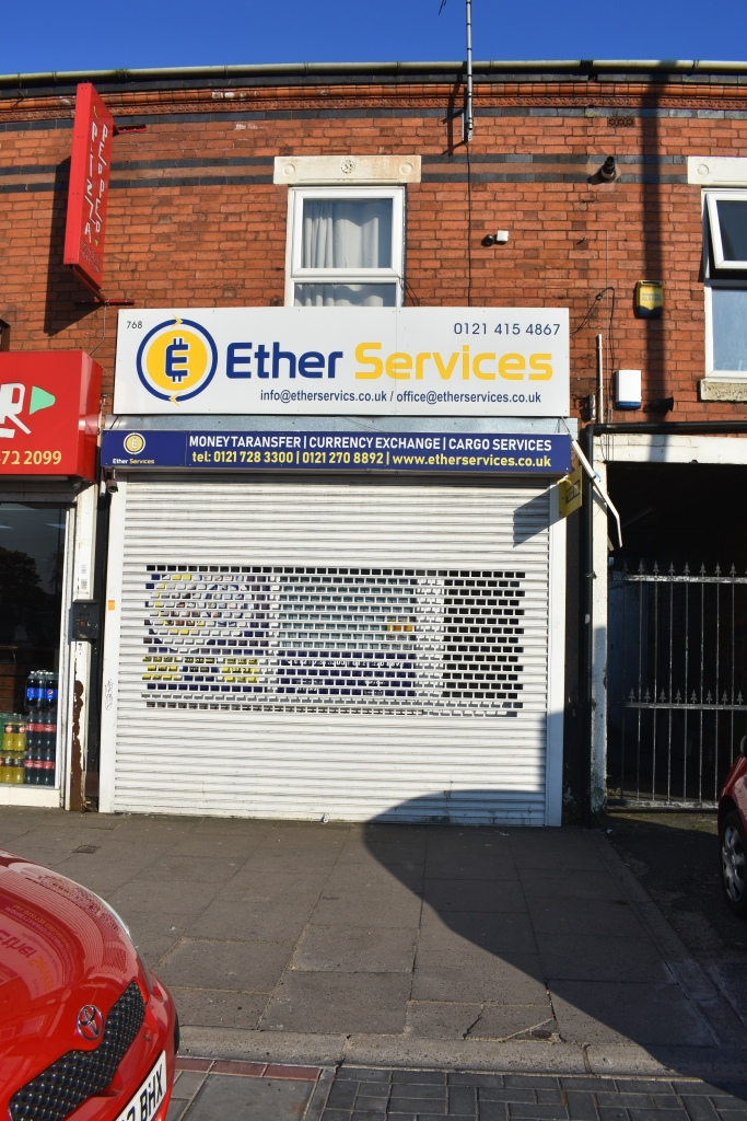 Picture of a two storey shop front with shutter in a terrace row