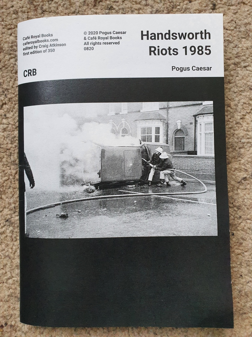 A6 sized book Black and white border, background and text saying that it is Handsworth Riots 1985, by Pogus Ceasar and edited by Craig Atkinson of Cafe Royal Books. Cover image is a black and white photograph of a small group of firefighters attempting to put out a fire that has been started in a car which has been turned on its side on a street of Victorian terraced houses